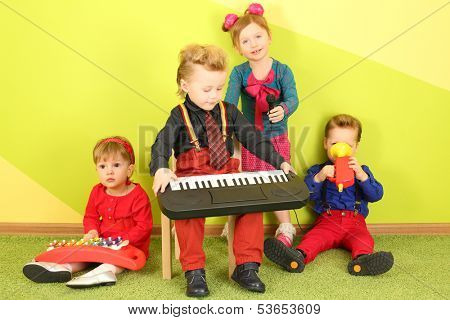 Four children with microphone and musical instruments: toy piano, metallophone and toy trumpet
