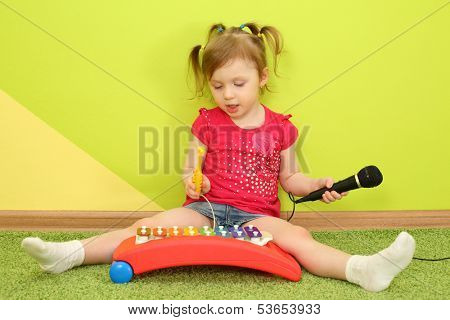 A girl with pigtails and a microphone in her hand playing on metallophone