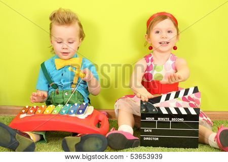 Boy with a metallophone and a girl with a clapstick sitting at the bright green wall