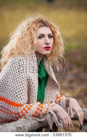 Beautiful woman posing in park during autumn season. Blonde girl wearing green blouse and big shawl