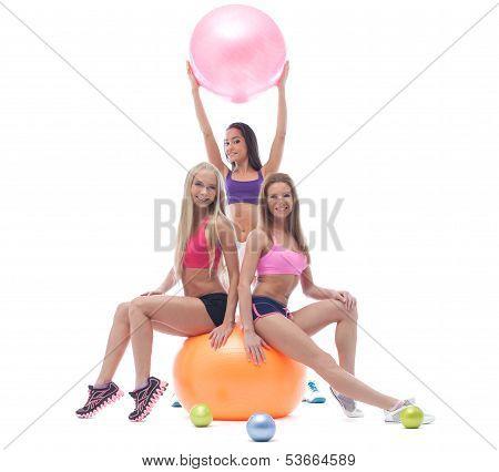 Trio of merry beautiful sportswomen in studio