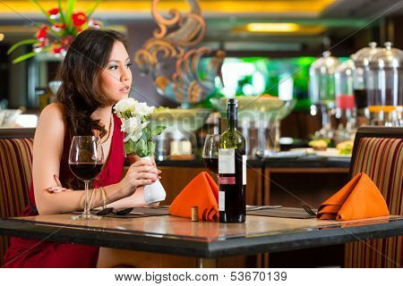 Chinese nervous, hoping, lonely, dreamy, heartsick woman in a restaurant waiting for a date got stood up