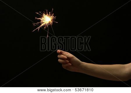 beautiful sparkler in woman hand on black background