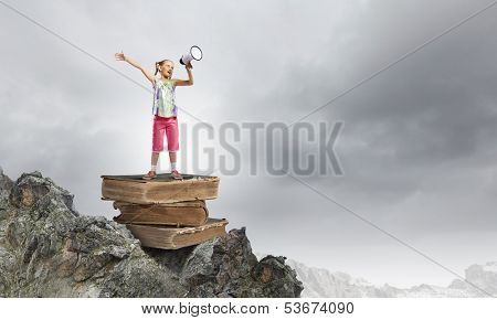 Image of cute school girl standing on pile of books
