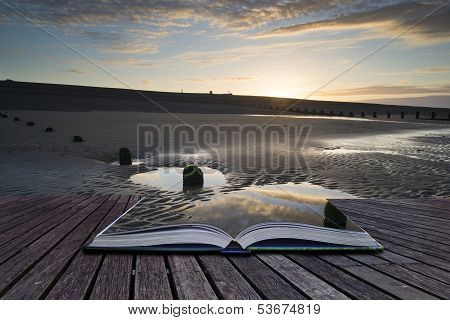 Creative Concept Pages Of Book Vibrant Sunrise Landscape Reflected In Low Tide Water On Beach
