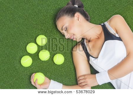 Female Tennis Player Lying On Artificial Grass Surface With Tennis Balls