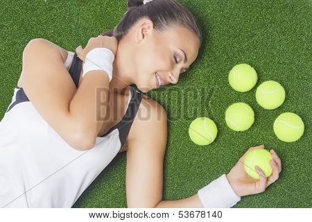 Portrait Of Dreaming Female Tennis Player Lying On Artificial Grass Surface With Tennis Balls