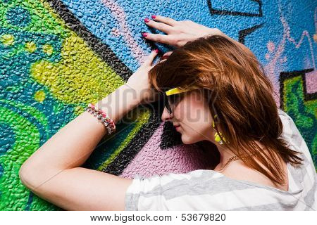 Stylish fashionable girl portrait against colorful graffiti wall. Fashion, trends, subculture.