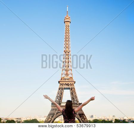 Young attractive happy woman with hands up facing the Eiffel Tower in Paris, France
