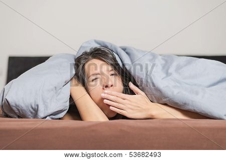 Tired Young Woman Yawning Under A Duvet