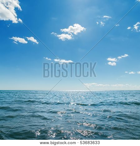 dark blue sea and deep blue sky with clouds