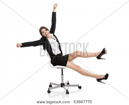 Happy business woman sitting on chair with arms up, isolated over white background
