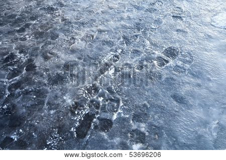 Pedestrians Footprints In Road Blue Ice. Street Sleet Background