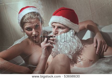 Portrait of handsome Santa cigar sitting in a hot bubble bath tub. Relaxing after a long night of deliveries with his girlfriend.
