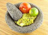 stock photo of pestle  - Molcajete mortar bowl and pestle filled with guacamole tomatoand lime on a wooden table - JPG