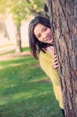 stock photo of shy woman  - portrait of shy young woman peaking from behind a tree and smiling