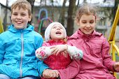 Cheerful boy and two girls in bright jackets on the swings at the playground