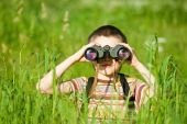 image of boy scout  - Young boy in a field looking through binoculars - JPG