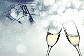 stock photo of flute  - Glasses with champagne against fireworks and clock close to midnight - JPG
