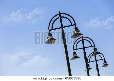 Modern light poles against a blue sky