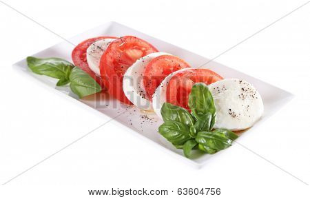 Caprese salad with mozarella cheese, tomatoes and basil on plate, isolated on white