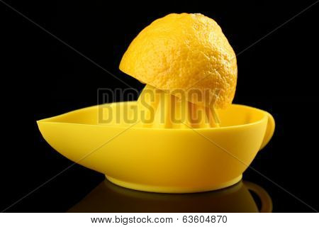 Citrus squeezer with lemon on black background