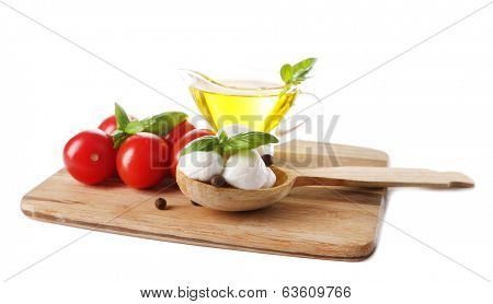 Composition with tasty mozzarella cheese balls, basil and red tomatoes, olive oil on cutting board, isolated on white