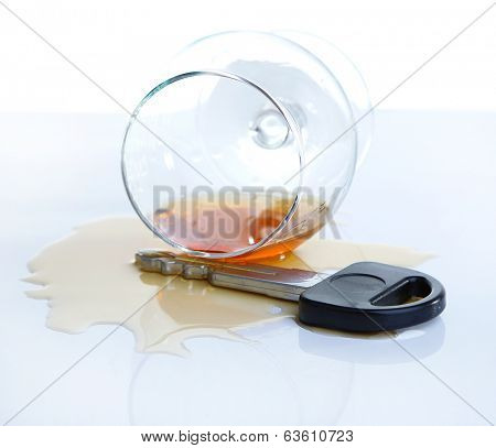 Composition with car key and glass of cognac, isolated on white