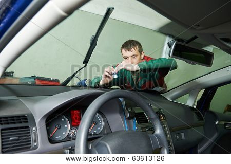 Automobile glazier repair windscreen or windshield of a car in auto service station garage