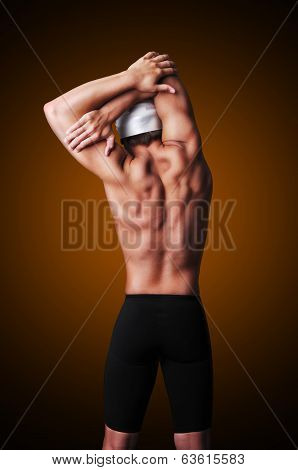 Muscular male swimmer posing with full equipment