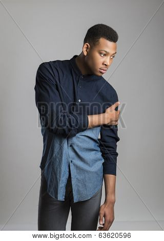 Portrait of handsome dark skinned male model wearing casual clothes against white background
