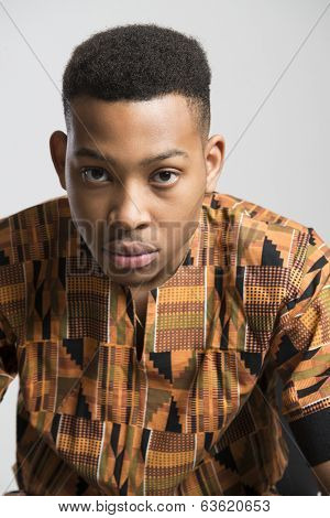 Portrait of handsome dark skinned male model wearing traditionally African clothes against white background