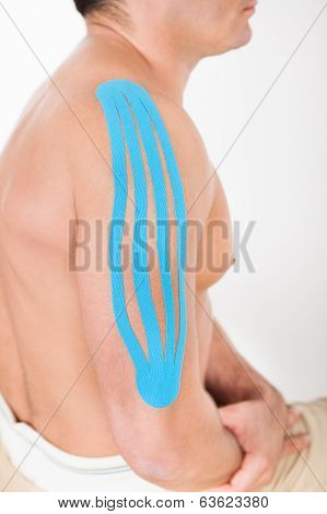 Young Man With Kinesio Tape Applied On Shoulder