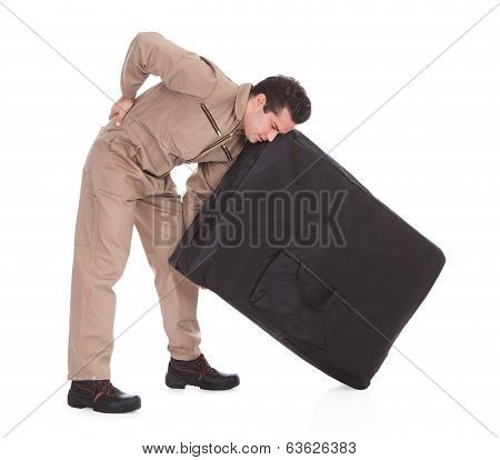 Man Suffering From Back Pain Lifting Luggage