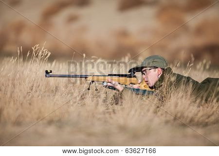 A young army cadet laying in the dry grass target shooting.