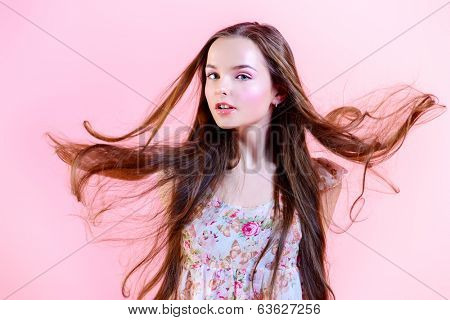 Elegant girl with natural make-up and beautiful long hair in motion posing over pink background. Fashion. Hairs.