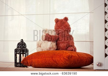 Two Embracing Loving Teddy Bears Sitting On Window-sill.