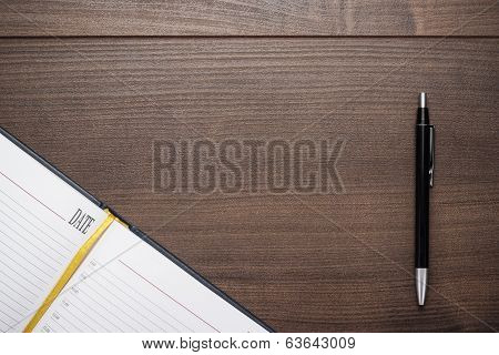 opened notebook and pen on wooden table