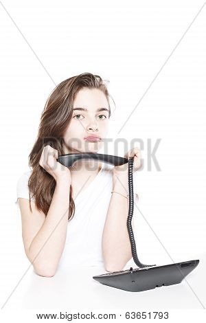 Sulking Female Teenager Holding Telephone Receiver In Both Hands, Isolated On White