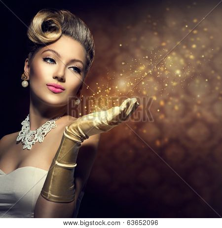 Retro Woman with magic in her hand. Beauty Fashion Vintage Style Lady with Beautiful Luxury Hairstyle, makeup, accessories. Golden Silk Gloves and dress