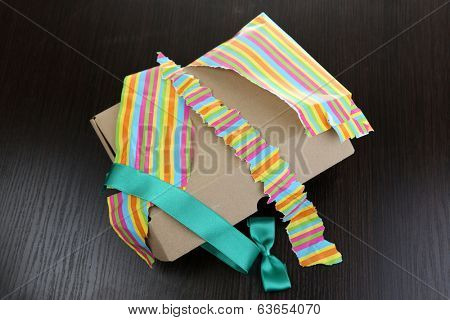 Unwrapped and opened gift box  on wooden background
