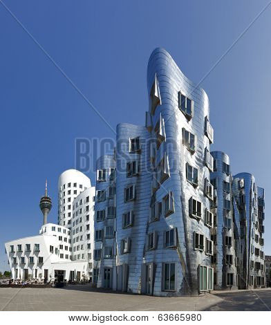 Dusseldorf, Germany - May 1, 2011: Frank O. Gehry's famous distorted buildings at Medienhafen Dusseldorf on a sunny day, Rheinturm tower in background.