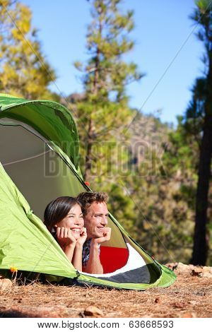 Camping couple in tent romantic looking at view in forest. Campers smiling happy outdoors in forest. Multiracial couple having fun relaxing after outdoor activity. Asian woman, Caucasian man.