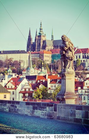 Vintage retro hipster style travel image of statue on Charles Brigde with St. Vitus Cathedral in background in Prague