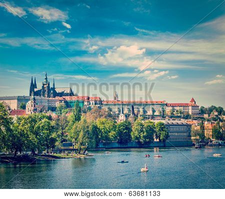 Vintage retro hipster style travel image of panorama view of Vltava river, Gradchany (Prague Castle) and St. Vitus Cathedral and Charles bridge an people in paddle boats in the Prague, Czech Republic