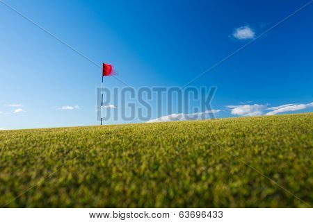 Red golf flag on a golf course, moving in the wind (motion blurred image); St. Andrews, Scotland