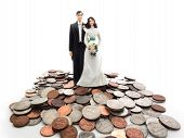 stock photo of plastic money  - Plastic wedding couple on a pile of coins  - JPG