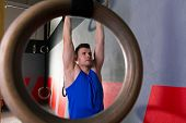 Rings workout man at gym muscle ups hanging