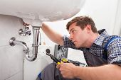 stock photo of bathroom sink  - Portrait of male plumber fixing a sink in bathroom - JPG