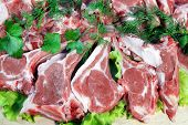 stock photo of lamb chops  - Fresh Lamb Chopped Rack on wooden cutting board - JPG